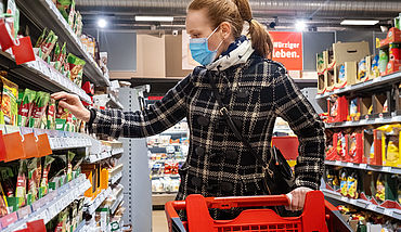 Woman grocery shopping with mask during the pandemic