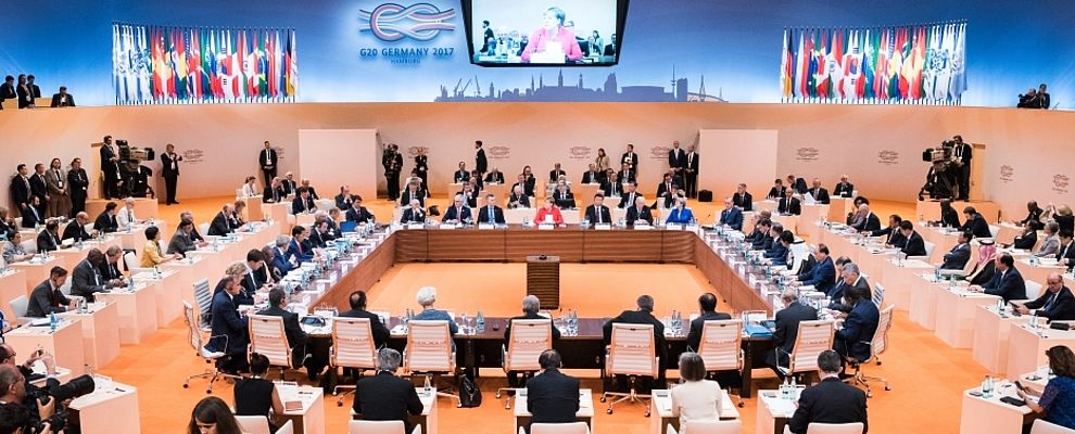 Overview of the G20 Summit 2017 in Hamburg. Angela Merkel is speaking in front of a great hall full of people sitting at their desks.