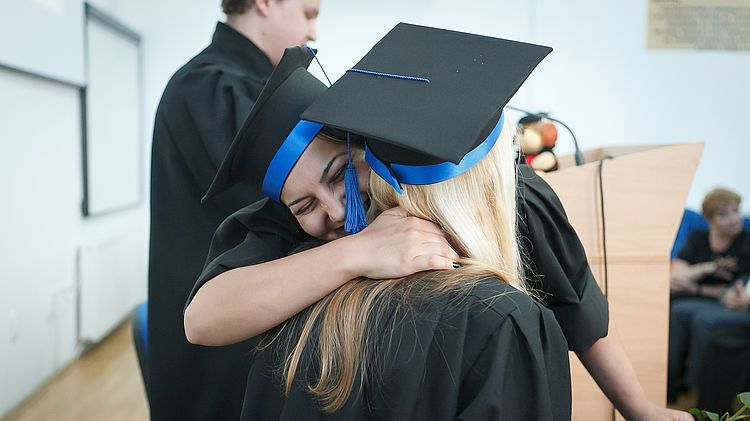 Two young women embrace to celebrate their graduation.