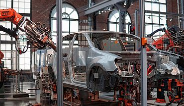 Car production line with robotic arms
