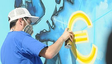 Graffiti artist spraying Euro sign on wall